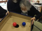 ホールインボールゲームに挑戦中!角度を変えながらボールを転がして、全部穴に落せるか?!